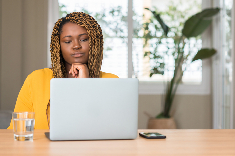 Woman with neutral expression looking at computer monitor
