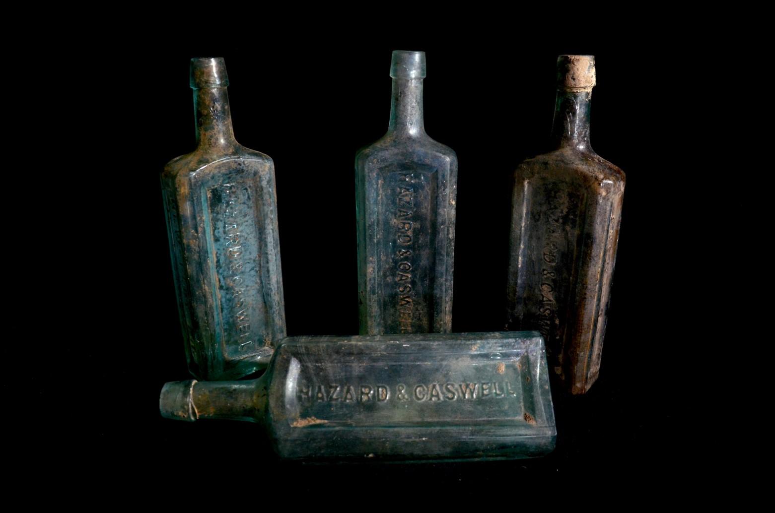 4 tarnished glass bottles read